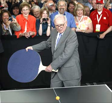 Warren Buffett plays table tennis using a giant paddle.