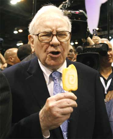 Buffett reacts after taking a bite of a Dairy Queen vanilla orange ice cream bar.