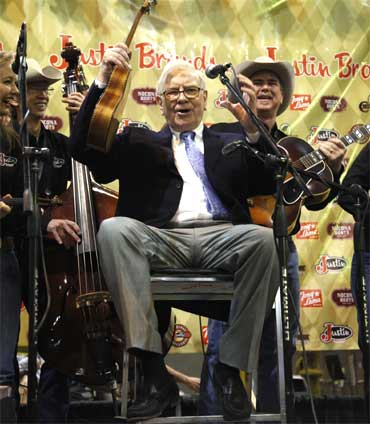 Buffett waves his ukulele with The Quebe Sisters Band. Buffett played I have Been Working on the Railroad.