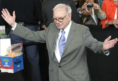 Buffett acknowledges the crowd after playing table tennis with world champion Ariel Hsing at the Berkshire Hathaway annual meeting weekend in Omaha.
