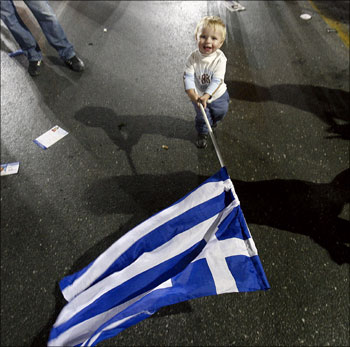 Image: A child waves a flag of Greece in Athens. Photograph: Reuters