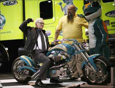 Billionaire financier and Berkshire Hathaway chief executive Warren Buffett poses on a motorcycle during the Berkshire Hathaway Annual Shareholders meeting in Omaha, Neb