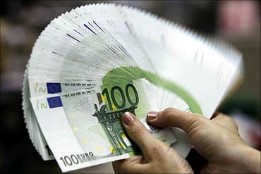 An employee counts Euro notes.