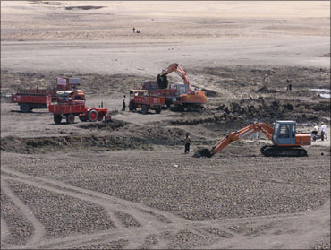 Trucks dredge the silt from the dried up bed of the lake Nakana near Aurangabad, near the Sendhra in