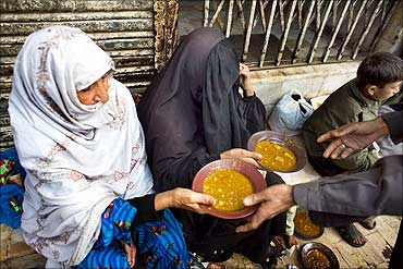 Women receive free food outside a restaurant in Karachi.