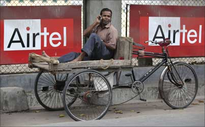 A man talks on a mobile phone in front of advertisements of Bharti Airtel.