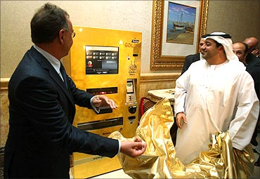 Ex Oriente Lux CEO Thomas Geissler (L) and an Emirati official unveil a gold-plated ATM.