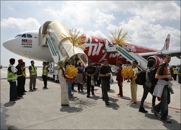 Passengers aboard AirAsia's maiden flight from London to Kuala Lumpur walk on the tarmac.