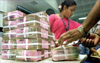 A bank staff is arranging stacks of rupee.