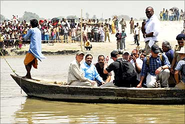 Microsoft Corp co-founder Bill Gates (front 2nd L) sits in a boat as he crosses river Kosi in Bihar.