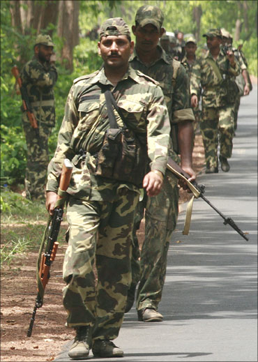 CRPF jawans march along a road in Chhattisgarh.