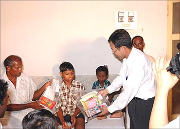 Posco official hands over books to children.