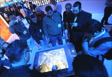 Visitors interact with Bing Maps at the Microsoft booth during the 2010 International Consumer Electronics Show in Las Vegas January 7, 2010.
