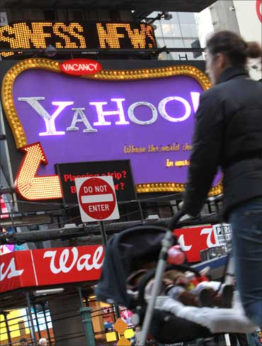 A woman walks in front of a Yahoo! billboard in New York's Time's Square January 25, 2010.