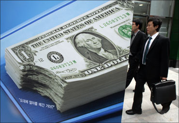 A yuan banknote is displayed behind a US dollar banknote for the photographer at a money changer's place.