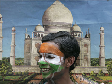 A schoolboy with his face painted in the colours of the Indian national flag stands in front of a photograph of the Taj Mahal.