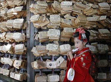A kimono-clad girl eats a candy as she visits Tokyo's Meiji Shrine.