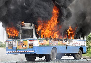 A passenger bus is set on fire during a protest by farmers demanding higher compensation for land.