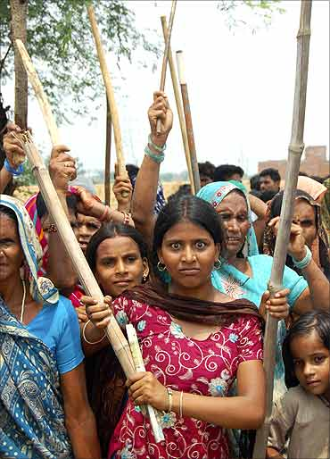 Stick-wielding protesters, mostly women, demonstrate as they demand higher compensation for land.