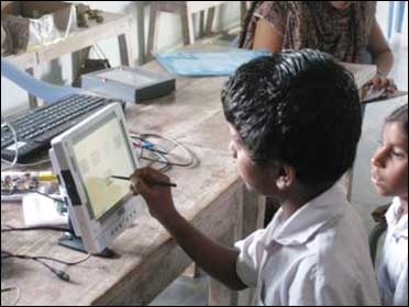 Children test a low-cost electronic notepad at a village school near Hyderabad