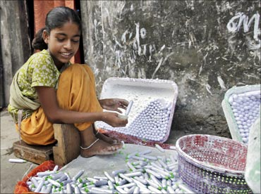 Laxmi packs lime paste tubes outside her house in a slum area in Mumbai.