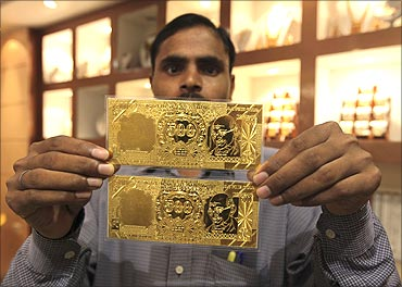 A salesman displays gold plates in the form of the Indian rupee note at a jewellery showroom.