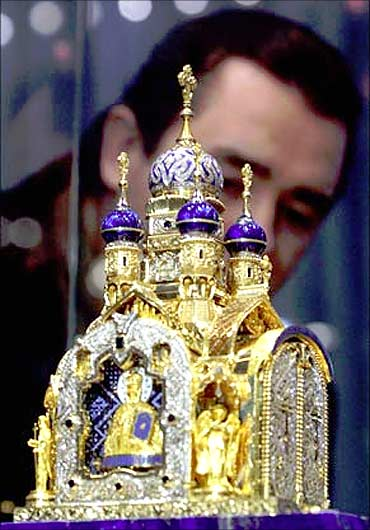 A visitor inspects a gold-and-jewel replica of a Russian Orthodox Church made by Russian artists.