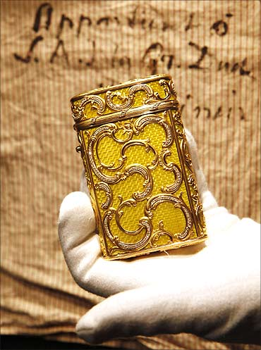 A worker holds a Faberge jewelled gold and enamel cigarette case by Michael Perchin in London.