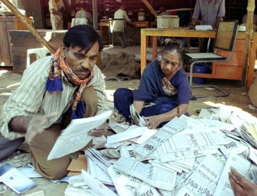 Postal employees sort mail in an open area at the main post office of Bhuj in Gujarat.