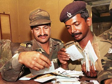 Indian soldiers search for their letters at a field post office in Kargil.