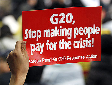 A demonstrator holds up a sign during an anti G20 protest in downtown Seoul.