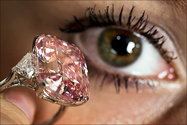 An employee poses with a 24.78 carat Fancy Intense Pink diamond at Sotheby's in Geneva.