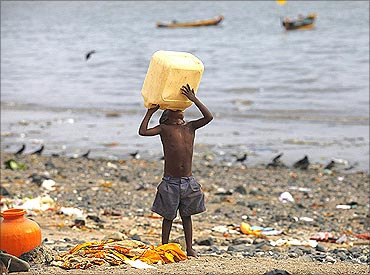 A homeless child tries to drink water from a plastic container on a beach in Mumbai.