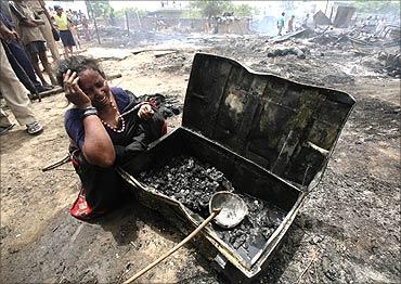 Urmila, a slum dweller, weeps besides her burnt belongings after a fire broke out in a slum area.