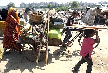 A family carries their belongings in a cycle rickshaw after they salvaged them from the debris.