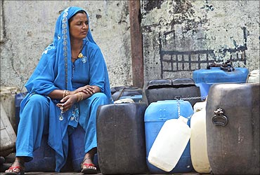 A woman sits on empty water buckets to be filled with drinking water.