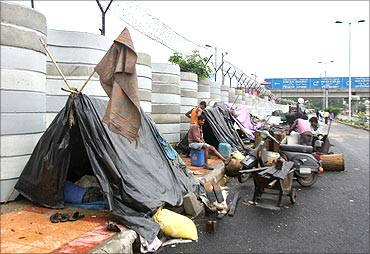 Labourers rest inside their makeshift tents outside the boundary wall of Commonwealth Games village.