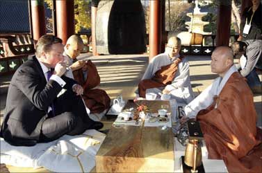 Britain's Prime Minister David Cameron (L) drinks tea with monks at the Bongeunsa temple in Seoul.