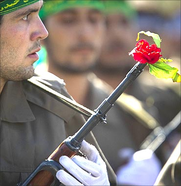 A member of Iran's Basij militia holds a gun with a rose on its muzzle during a parade in Tehran.
