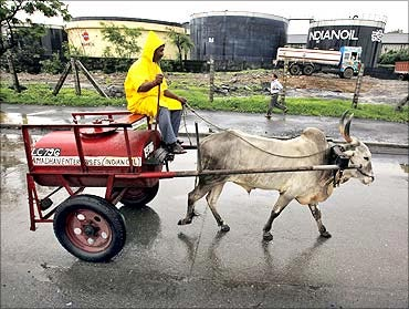 A worker transporting kerosene in a bullock cart travels past Indian Oil Corporation's fuel depot.