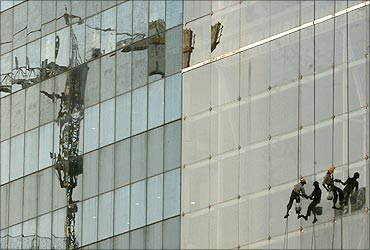 Workers clean the window of a building.