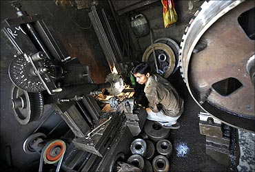 A worker makes gear parts for cranes at a workshop in Mumbai.