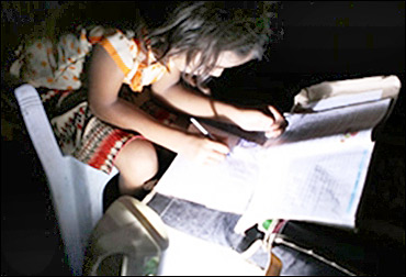 A child studies with a solar lamp.