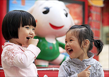 Two children pose in front of the Asian Games mascot in Guangzhou.
