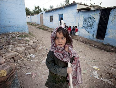 Seven-year-old Shamsa stands outside her house in a village in Noor Pur Shahan.