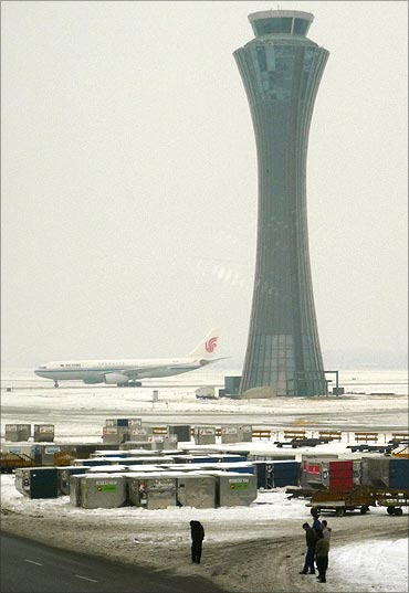 Airport workers standing out on the snow-covered tarmac at Beijing airport.