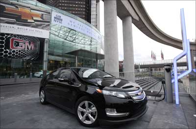 A Chevrolet Volt electric vehicle sits plugged into a charging station in front of GM's headquarters.