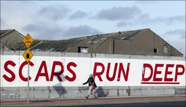 A pedestrian walks past graffiti in Dublin.