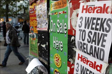 A man walks past newspaper headlines posted on a news stand on O'Connell Street, Dublin.
