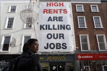A pedestrian walks past sign protesting against high rents on Grafton Street in Dublin.